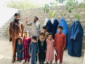 Mohammed Jafar poses for a picture along with widows of his three brothers, their children and his father, in Kunar