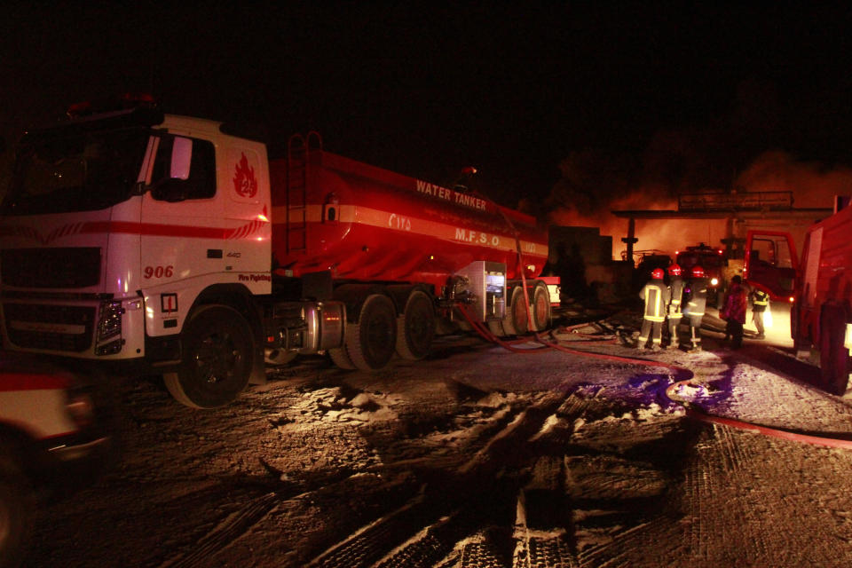 Iranian firefighters work on a burning tanker carrying fuel at the Islam Qala border with Iran, in Herat Province, west of Kabul, Afghanistan, Saturday, Feb. 13, 2021. The fuel tanker exploded Saturday at the Islam Qala crossing in Afghanistan's western Herat province on the Iranian border, injuring multiple people and causing the massive fire that consumed more than 500 trucks carrying natural gas and fuel, according to Afghan officials and Iranian state media. (AP Photo/Hamed Sarfarazi)