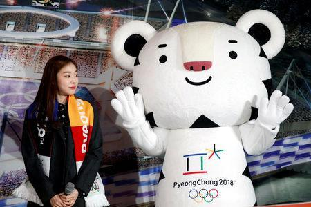 """FILE PHOTO - The PyeongChang Organizing Committee for the 2018 Olympic and Paralympic Winter Games (POCOG) Honorary Ambassador Kim Yuna looks at the Olympic mascot """"Soohorang"""" during the ceremony to mark a year to the 2018 PyeongChang Winter Olympic Games in Gangneung, South Korea February 9, 2017. REUTERS/Kim Hong-Ji/File Photo"""