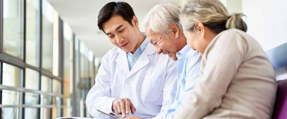 young doctor discussing test results with smiling older couple