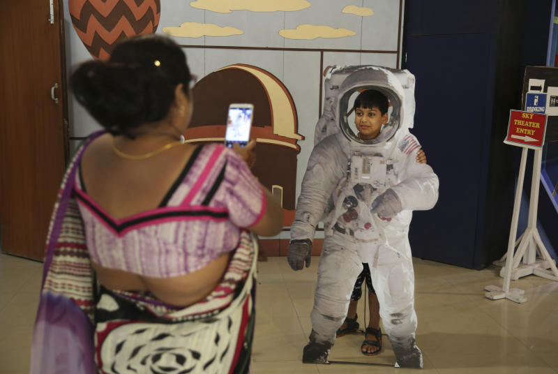 An Indian woman takes a photograph of her son as he poses in a cut-out of an astronaut at the Nehru Planetarium in New Delhi, India, Thursday, July 11, 2019. India is looking to take a giant leap in its space program and solidify its place among the world's spacefaring nations with its second unmanned mission to the moon, this one aimed at landing a rover near the unexplored south pole. (AP Photo/Altaf Qadri)
