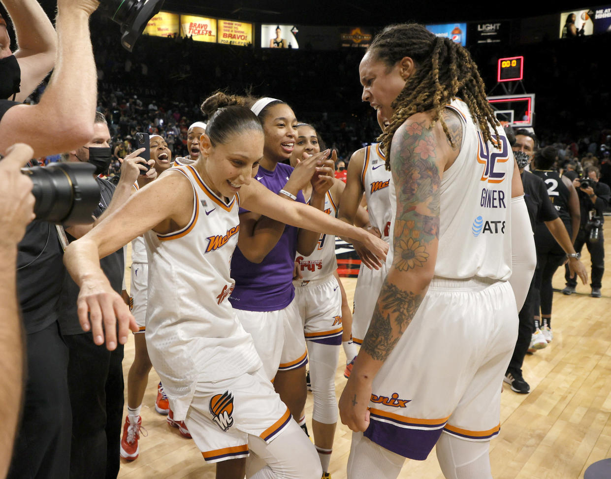 Diana Taurasi falls backward while celebrating with Brittney Griner, who is yelling in excitement, after the Mercury won Game 5 of the WNBA semifinals series against the Aces.