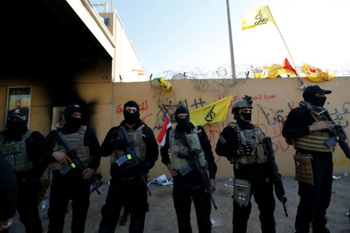 Members of Iraqi security forces stand guard as protesters and militia fighters gather to condemn air strikes on bases belonging to Hashd al-Shaabi (paramilitary forces), outside the main gate of the U.S. Embassy in Baghdad