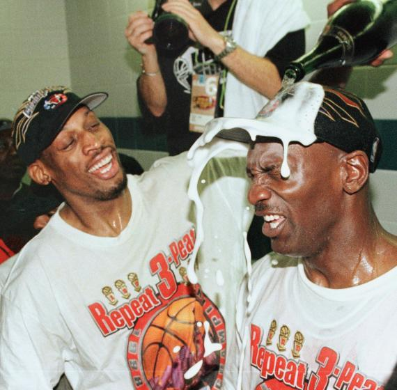 """Dennis Rodman pours champagne on the head of teammate Michael Jordan after the Chicago Bulls won the 1998 NBA championship. <span class=""""copyright"""">(Mike Nelson / AFP via Getty Images)</span>"""