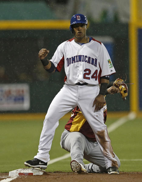 Dominican Republic's Robinson Cano celebrates after reaching third beating the throw of Venezuela's shortstop Elvis Andrus in the first inning of their World Baseball Classic first round game in San Juan, Puerto Rico, Thursday, March 7, 2013. (AP Photo/Andres Leighton)