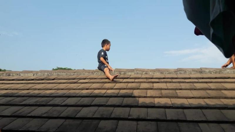 An Indonesian boy stays up on a roof for three hours to avoid getting circumcised. ― Picture via Facebook/anik.sutari.5