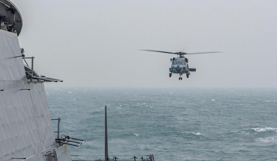 The US Navy released pictures of a helicopter taking off and landing on the deck during the passage. Photo: Handout