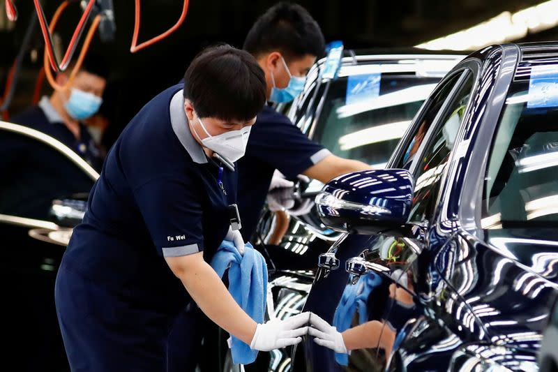 FILE PHOTO: Employees wearing face masks work at a Beijing Benz Automotive Co plant in Beijing