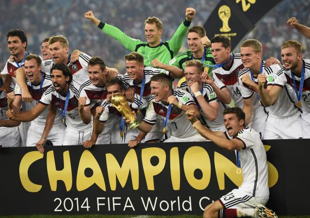 Germany's Bastian Schweinsteiger (7) holds the World Cup trophy as he celebrates with teammates after the 2014 World Cup final against Argentina at the Maracana stadium in Rio de Janeiro July 13, 2014. REUTERS/Dylan Martinez (BRAZIL - Tags: SOCCER SPORT WORLD CUP) TOPCUP