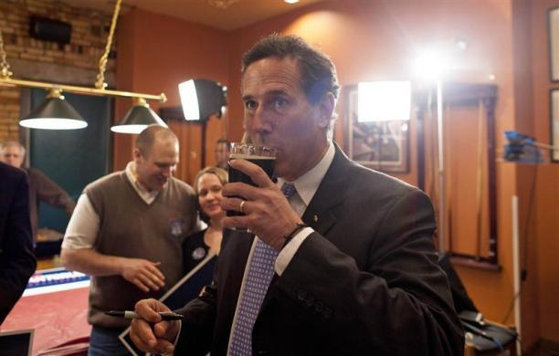 Rick Santorum drinks a beer after talking to the media as the polling numbers for the Louisiana primary come in at Title Town Brewery in Green Bay, Wisconsin, March 24, 2012.