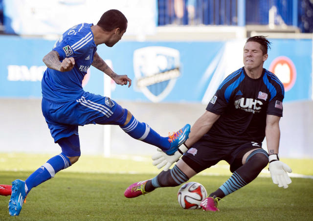 Montreal Impact's Andres Romero, left, scores against New England Revolution's Bobby Shuttleworth during first half MLS soccer action in Montreal, Saturday, May 31, 2014. (AP Photo/The Canadian Press, Graham Hughes)