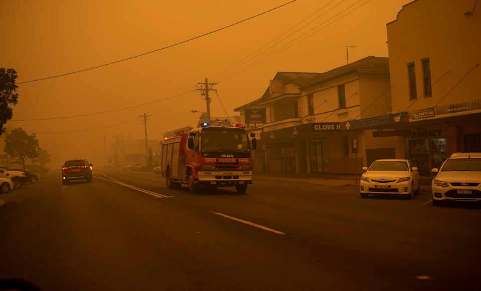 A fire truck moves up the main street of the New South Wales town of Bombala which is shrouded in smoke from nearby bushfires on December 31, 2019. - Thousands of holidaymakers and locals were forced to flee to beaches in fire-ravaged southeast Australia on December 31, as blazes ripped through popular tourist areas leaving no escape by land. (Photo by SEAN DAVEY / AFP) (Photo by SEAN DAVEY/AFP via Getty Images)