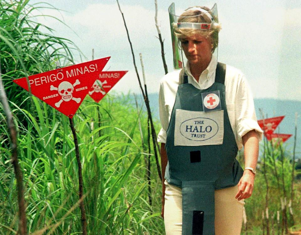 Diana Princess of Wales walks through a safety corridor in a land mine field in Huambo January 15. Diana is on a four day visit to Angola at the invitation of the British Red Cross to help increase awarness of the landmines problem world wide. The signs say