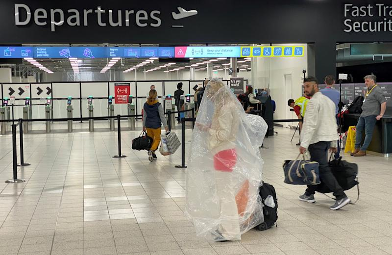 A passenger covered with a plastic bag is seen at Luton Airport, following the outbreak of the coronavirus disease, Luton, Britain, June 4, 2020. REUTERS/Paul Childs