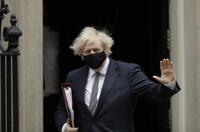 British Prime Minister Boris Johnson waves at the media as he leaves 10 Downing Street in London, to attend the weekly Prime Minister's Questions at the Houses of Parliament, in London, Wednesday, March 24, 2021. (AP Photo/Matt Dunham)