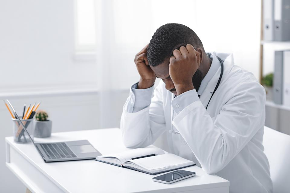 Exhausted young african doctor sitting in office in front of laptop, having headache, copy space