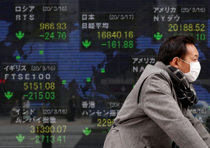 A man wearing a protective face mask walks past a screen displaying the world's markets indices outside a brokerage in Tokyo