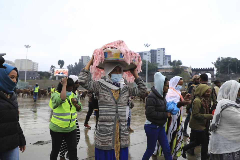 Women bring food to give to the youth joining the Defense Forces, at Meskel Square, in Addis Ababa, Ethiopia, Tuesday, July 27 2021. A repatriation program is underway for young people from Ethiopia who have decided to join the Defense Forces. (AP Photo)