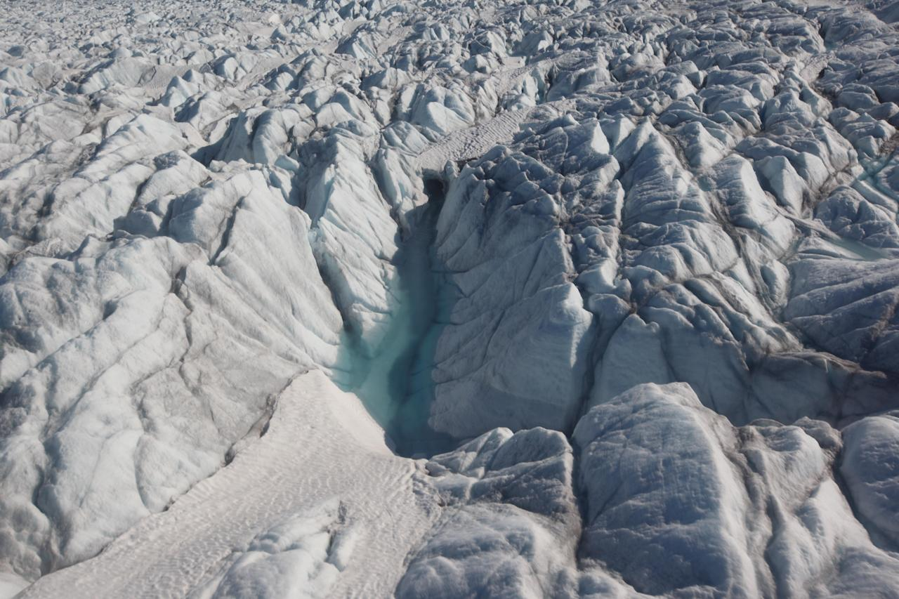 In this July 19, 2011 photo, a pool of melted ice forms atop Jakobshavn Glacier, at the fringe of the Greenland ice sheet. (AP Photo/Brennan Linsley)