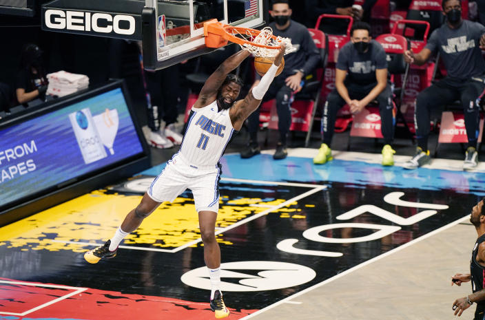 Orlando Magic forward James Ennis III (11) hangs from the rim after dunking unopposed during the first quarter of an NBA basketball game against the Brooklyn Nets, Thursday, Feb. 25, 2021, in New York. (AP Photo/Kathy Willens)