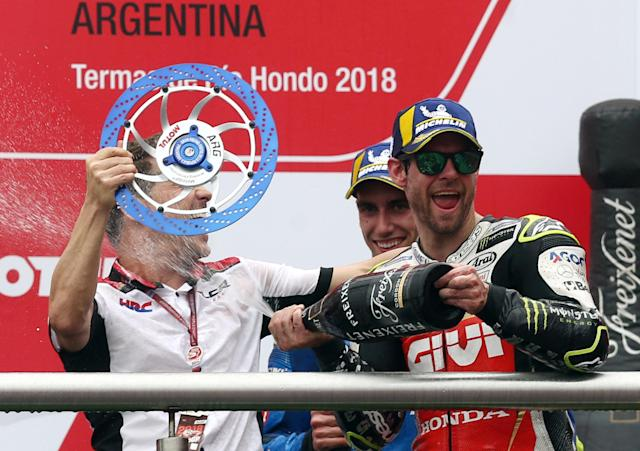 Motorcycle Racing - Argentina Motorcycle Grand Prix - MotoGP race - Termas de Rio Hondo, Argentina - April 8, 2018 - LCR Honda Castrol rider Cal Crutchlow of Britain sprays champagne over his team manager Lucio Cecchinello, in front of Team Suzuki Ecstar rider Alex Rins of Spain, on the podium. REUTERS/Marcos Brindicci