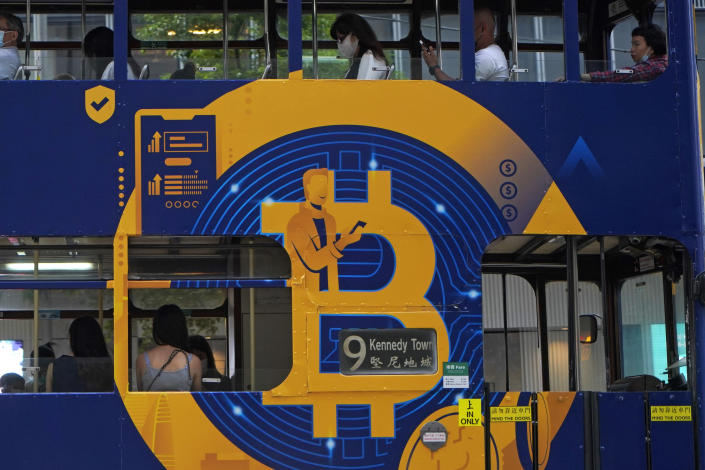 FILE - In this May 12, 2021, file photo, an advertisement of Bitcoin, one of the cryptocurrencies, is displayed on a tram in Hong Kong. China's biggest banks promised Monday, June 21, 2021, to refuse to help customers trade Bitcoin and other cryptocurrencies after the central bank said executives were told to step up enforcement of a government ban. (AP Photo/Kin Cheung, File)