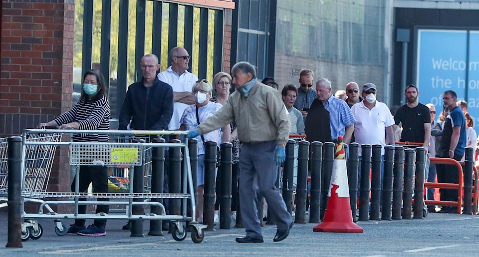People queue outside a B&Q in Wallasey, Wirral. as the UK continues in lockdown to help curb the spread of the coronavirus.