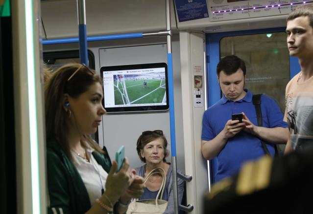 Commuters are seen in a metro coach as an electronic screen shows a live broadcast of the 2018 World Cup match between Denmark and Australia in Moscow, Russia June 21, 2018. REUTERS/Tatyana Makeyeva