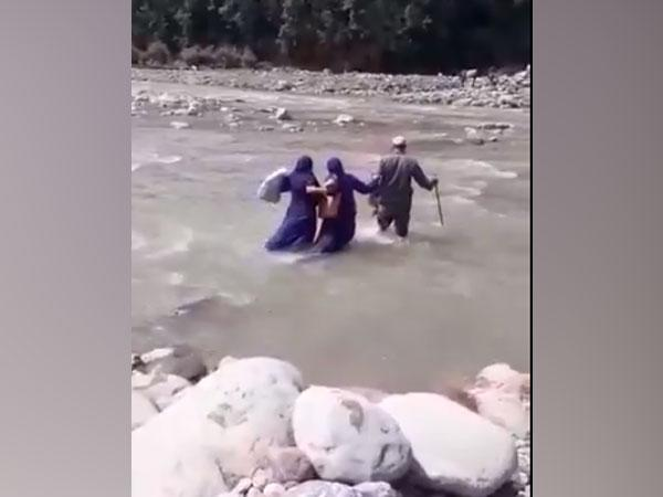 Healthcare workers in Jammu and Kashmir's Rajouri crossing a river to conduct COVID-19 vaccination drive. (Photo/ ANI)