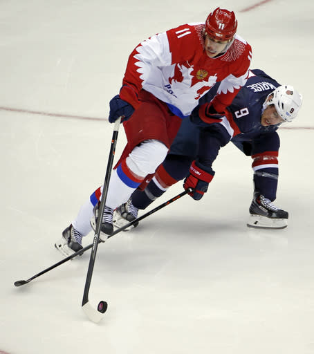 Russia forward Yevgeni Malkin and USA forward Zach Parise battle for the puck in the third period of a men's ice hockey game at the 2014 Winter Olympics, Saturday, Feb. 15, 2014, in Sochi, Russia. (AP Photo/Petr David Josek)