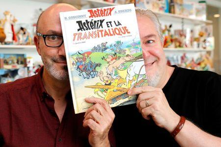 "Author Jean-Yves Ferri (L) and illustrator Didier Conrad (R) pose with a copy of their new comic album ""Asterix et la Transitalique"" (Asterix and the Chariot Race) after an interview in Vanves near Paris, France, October 17, 2017, the latest in the series created by illustrator Albert Uderzo and writer Rene Goscinny in 1959. Picture taken October 17, 2017.   REUTERS/Philippe Wojazer"