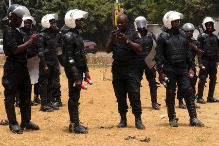 Police officers hold tear gas canisters during an opposition rally in Conakry