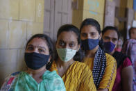 Indian women wearing face masks as precaution against COVID-19, stand in queue to cast their vote for local body elections in Ahmedabad, India, Sunday, Feb. 21, 2021. (AP Photo/Ajit Solanki)