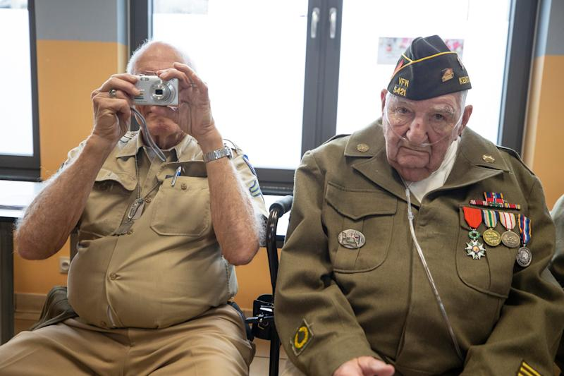 World War II veteran Frank Riesinger takes a photo while fellow vet and Louisville native George Merz looks straight ahead during a visit Dec. 13, 2019, to the Noville, Belgium, public school.