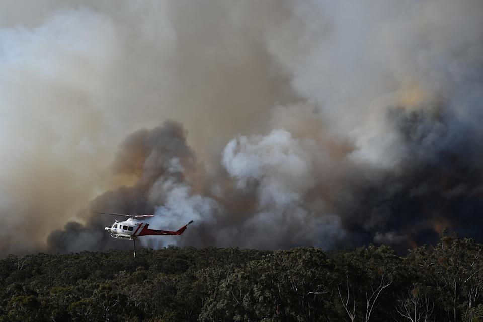A water bombing helicopter at the Gospers Mountain fire near Colo Heights south west of Sydney in November. Source: AAP