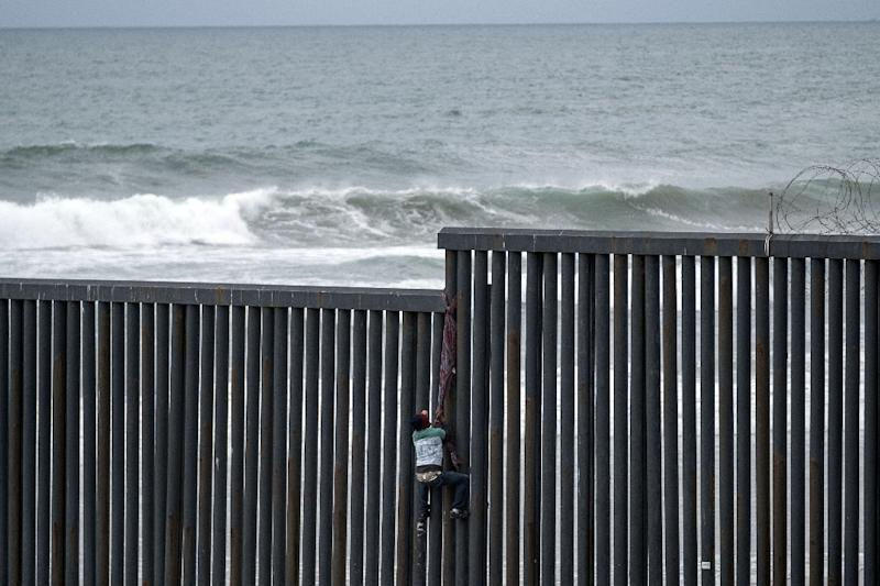 A Central American tries to climb the US-Mexico border fence to San Diego, California (AFP Photo/Guillermo Arias)