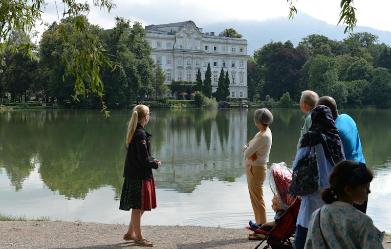 Tourists stand in front of the Leopoldskron Palace where part of the film 'Sound of Music' was shot, in Salzburg, Austria on August 1, 2014