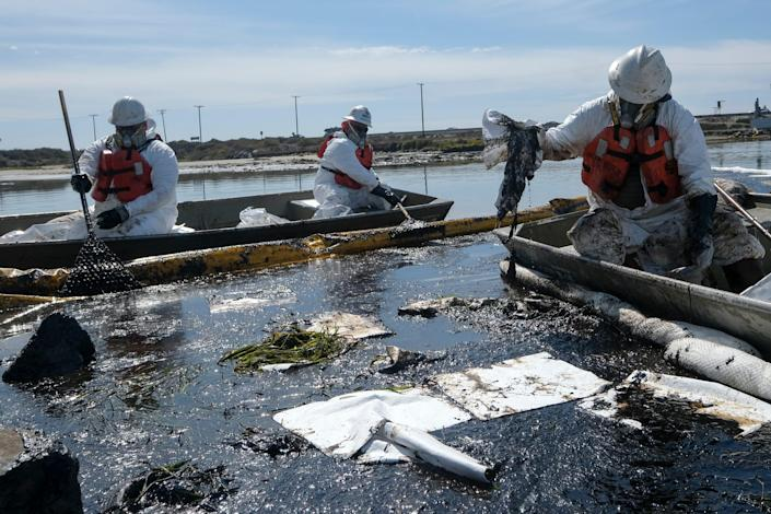 Cleanup contractors deploy skimmers and floating barriers known as booms to try to stop further oil crude incursion into the Wetlands Talbert Marsh in Huntington Beach, Calif., on Oct. 3. One of the largest oil spills in recent Southern California history fouled popular beaches and killed wildlife while crews scrambled to contain the crude.