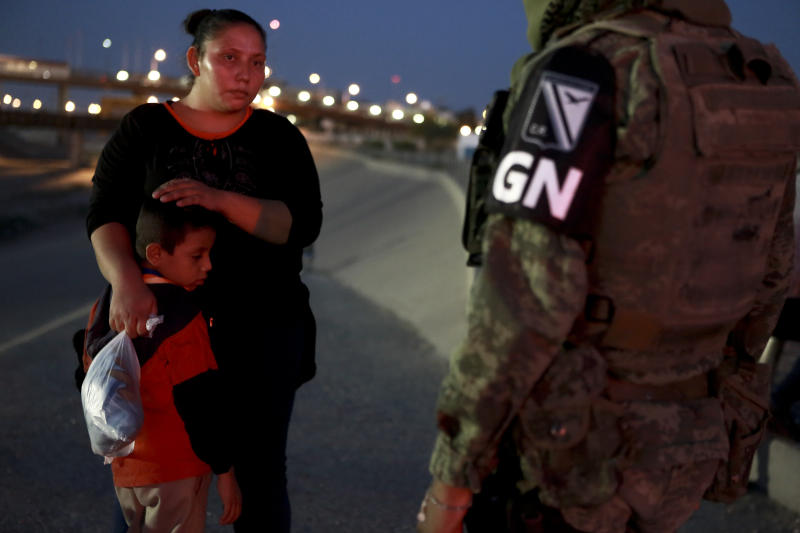 FILE - In this June 24, 2019 file photo, a military police officer wearing the insignia of Mexico's new National Guard detains Guatemalan migrants to keep them from crossing from Ciudad Juarez, Mexico to El Paso, Texas. Under pressure from the U.S. government, Mexico's immigration policy has moved from promising to help migrants, to one characterized by militarized enforcement under the growing influence of the country's Foreign Secretary Marcelo Ebrard. (AP Photo/Christian Chavez, File)