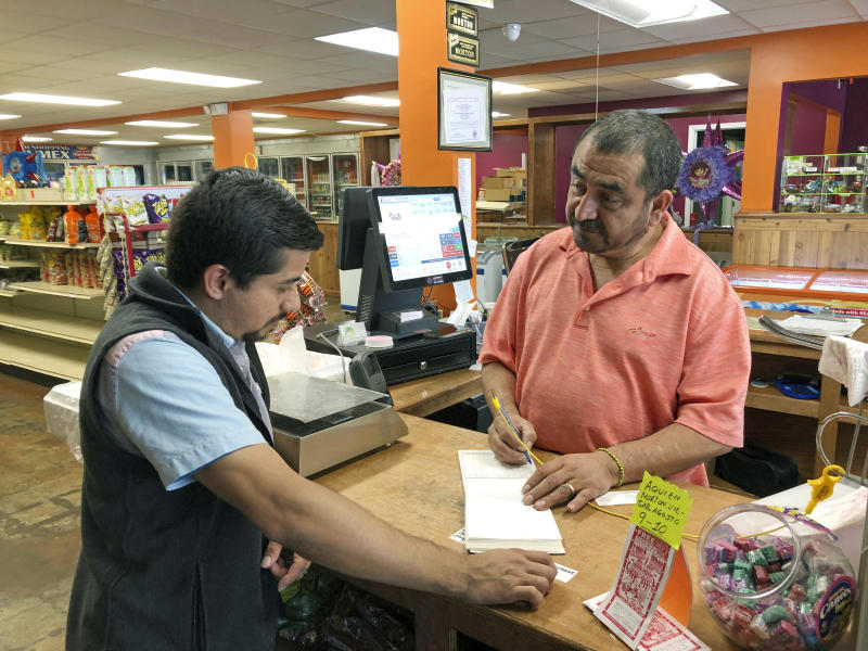 In this Thursday, Aug. 8, 2019 photo, owner Juan Garcia, right, waits on a customer at Hondumex in downtown Morton, Miss. Garcia says he's considering closing his store after Wednesday's immigration arrests at the town's Koch Foods poultry plant. The raids were part of a large-scale operation targeting owners as well as undocumented employees. (AP Photo/Jeff Amy)