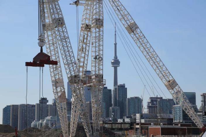 The downtown skyline and CN Tower are seen past cranes in the waterfront area of Toronto