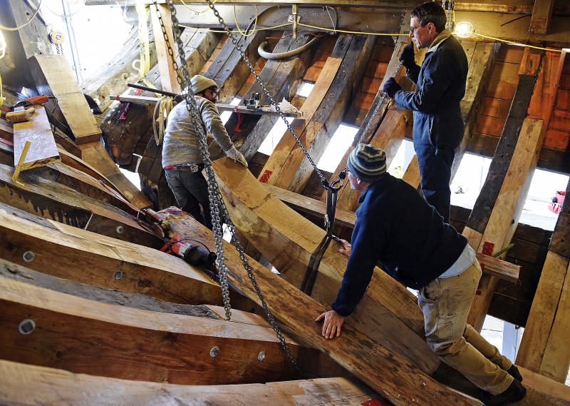 In this Nov. 8, 2017 photo, shipwrights Trevor Allen, top right, Chris Taylor, bottom right, and Krityavijay Singh move the stern knee into position to check the fit in the hold of the Mayflower II at Mystic Seaport's H.B. duPont Preservation Shipyard in Mystic, Conn. Restoration of the ship, a replica of the vessel that brought Pilgrims to Massachusetts in 1620, is expected to be completed in 2019 when it will return to its home port in Plymouth, Mass. (Sean D. Elliot/The Day via AP)