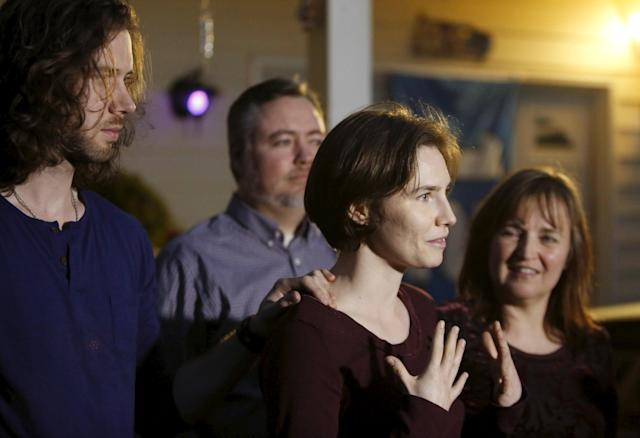 Amanda Knox (2nd R) talks to the press, flanked by her her fiance Colin Sutherland (L), mother Edda Mellas and stepfather Chris Mellas, outside her mother's home in Seattle, Washington March 27, 2015. Italy's top court on Friday annulled the conviction of American Amanda Knox for the 2007 murder of British student Meredith Kercher and, in a surprise verdict, acquitted her of the charge. The Court of Cassation threw out the second guilty verdict to have been passed on Knox, 27, and her Italian former boyfriend Raffaele Sollecito for the lethal stabbing. REUTERS/Jason Redmond