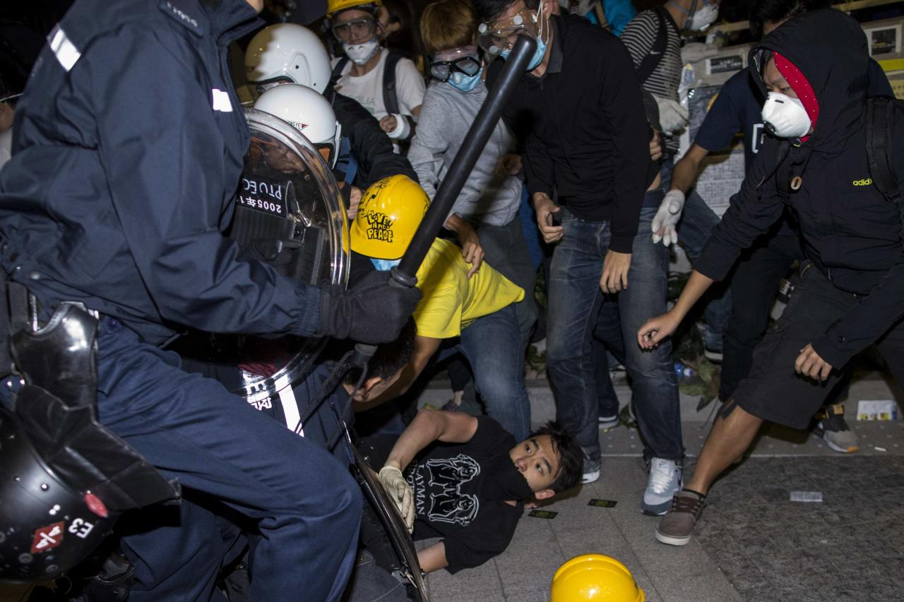 A protester falls on the ground as they are chased by riot police outside the Legislative Council in Hong Kong early November 19, 2014.A small group of Hong Kong pro-democracy protesters broke into the city's legislature via a side door early on Wednesday, and police stopped others storming the building as tensions jumped following a period of calm. REUTERS/Tyrone Siu (CHINA - Tags: POLITICS CIVIL UNREST EDUCATION)