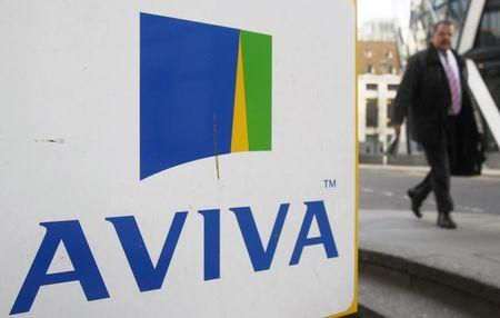 A man walks past an AVIVA logo outside the company's head office in the city of London