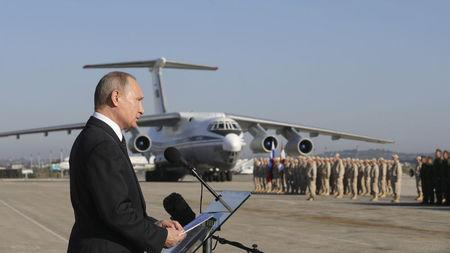 FILE PHOTO: Russian President Putin addresses servicemen as he visits the Hmeymim air base in Latakia Province