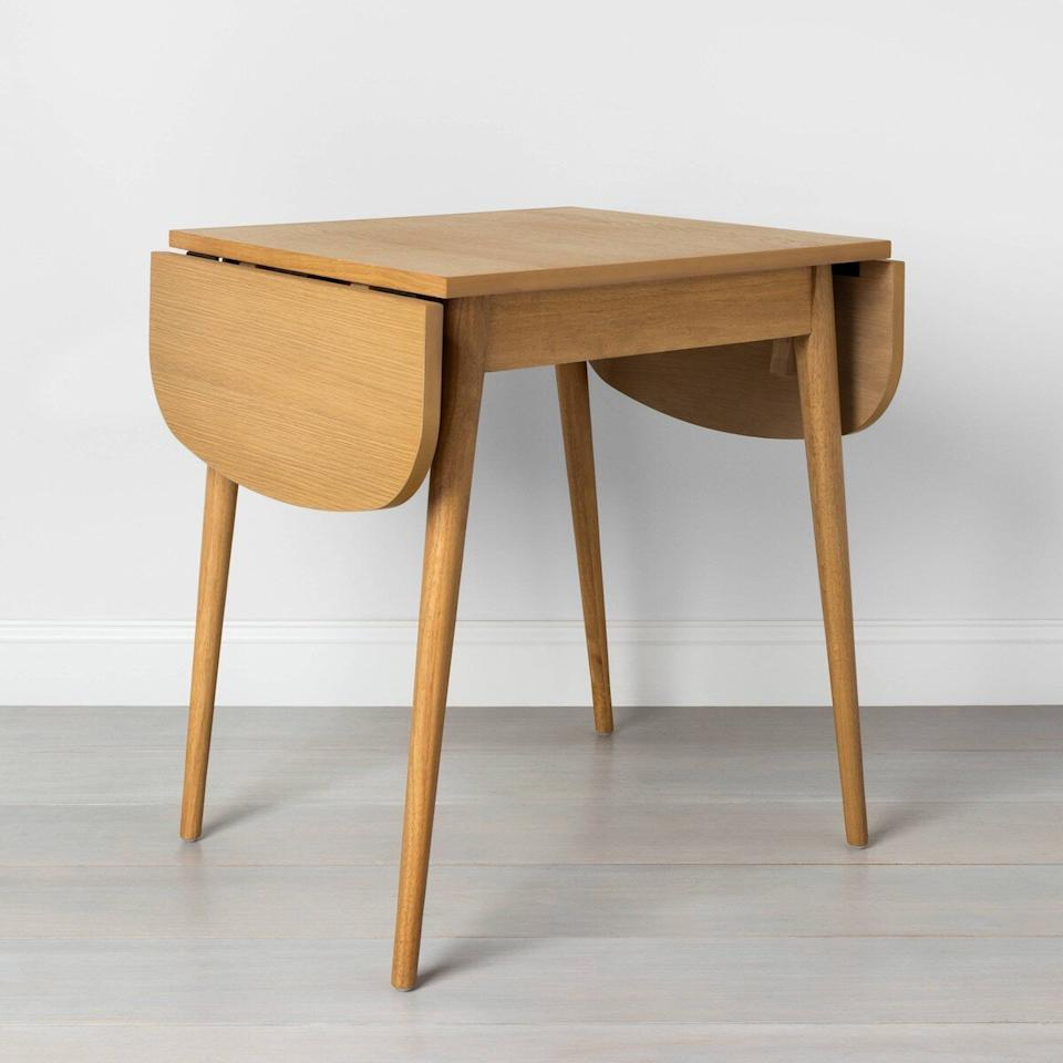 """<p>If you hardly have space for a dining table, this expandable option will help you save space. When it's time for dinner, open up the two leaves. When the meal is over, the leaves drop down to maximize square footage. </p> <p><strong>To buy: </strong>$200, <a href=""""http://goto.target.com/c/249354/81938/2092?subId1=RS%2CJoannaandChipGaines%2527sTargetLineIsNearlyDoublingInSize%25E2%2580%2594Our5NewFavorites%2Ckholdefehr1271%2CDEC%2CIMA%2C695189%2C202003%2CI&u=https%3A%2F%2Fwww.target.com%2Fp%2Ffolding-bistro-table-hearth-38-hand-with-magnolia%2F-%2FA-76845031"""" target=""""_blank"""">target.com</a>. </p>"""
