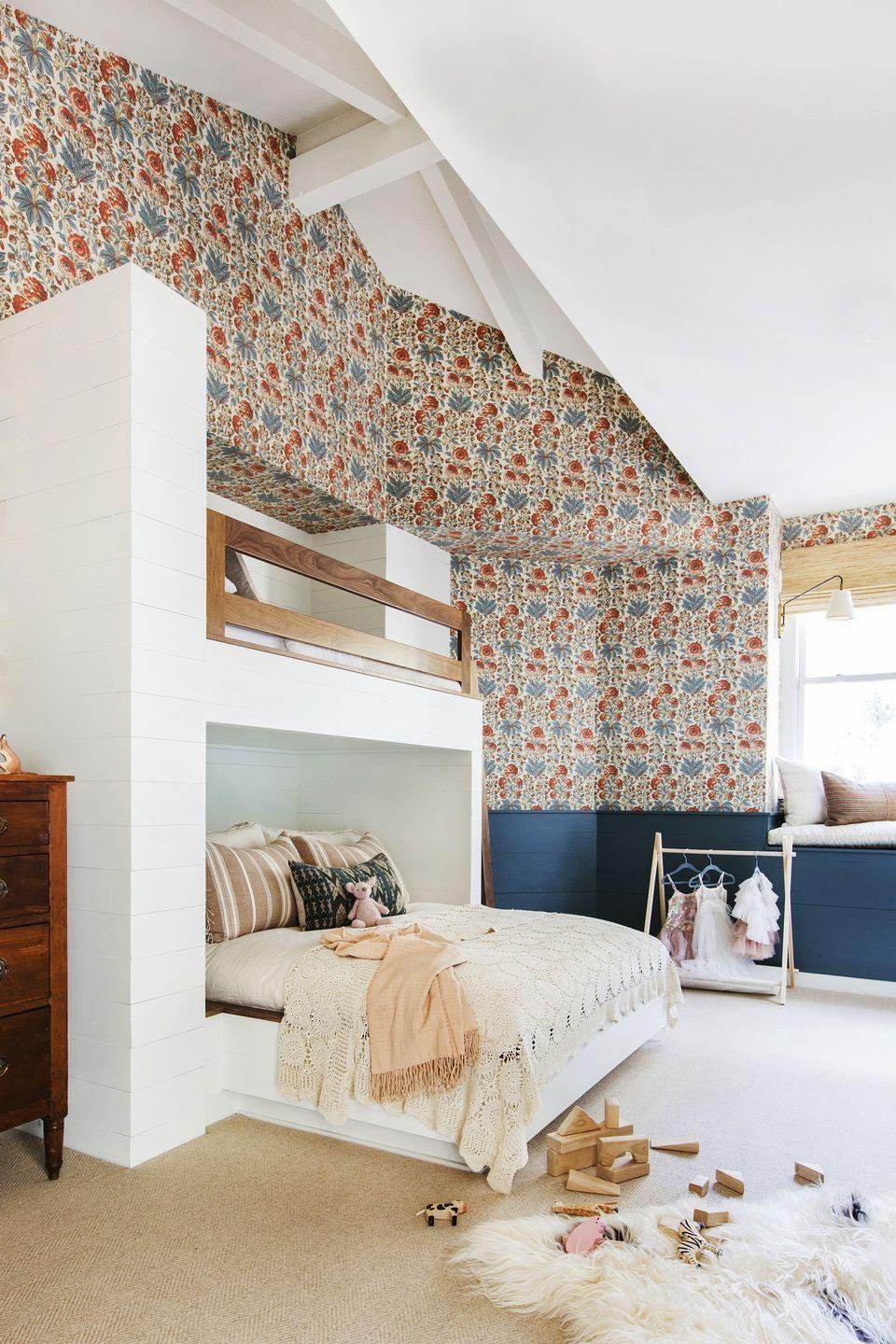 <p>Sometimes, boho-inspired bedrooms are light and bright. This bedroom, however, mixes light and dark: a white bunk bed pops against coral and navy wallpaper.</p>