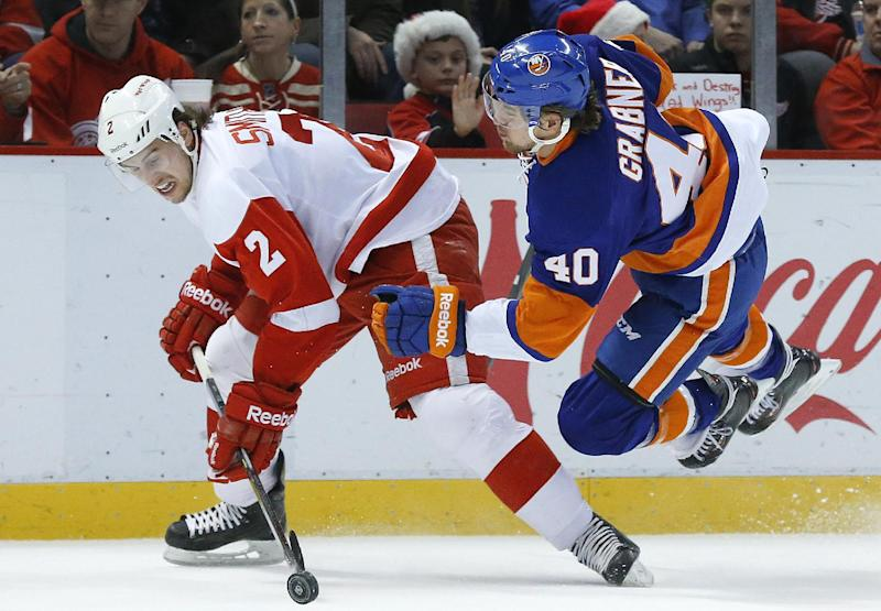 Detroit Red Wings defenseman Brendan Smith (2) takes New York Islanders right wing Michael Grabner (40), of Austria, off the puck in the first period of an NHL hockey game, Monday, Dec. 23, 2013, in Detroit. (AP Photo/Paul Sancya)
