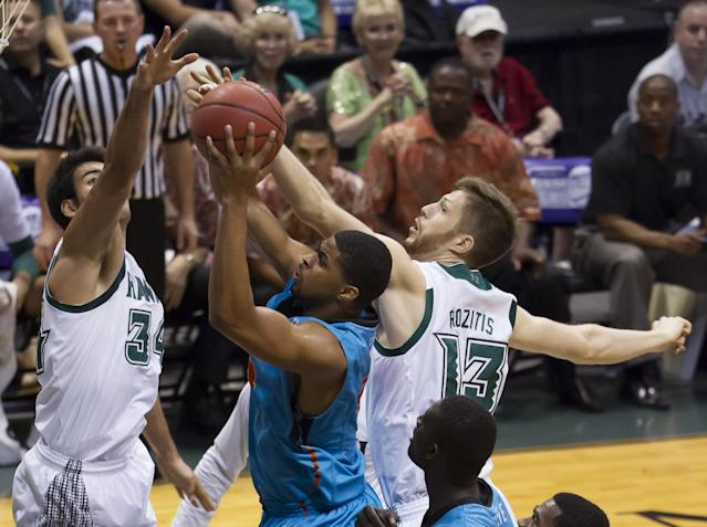 Hawaii forward Christian Standhardinger, left, and center Davis Rozitis (13) attempt to block the shot of Oregon State forward Devon Collier during the first half of an NCAA college basketball game at the Diamond Head Classic on Wednesday, Dec. 25, 2013, in Honolulu. (AP Photo/Eugene Tanner)